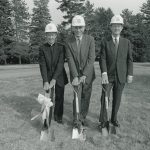 Fr. Monan & 2 other men pose with feet poised on shovels.