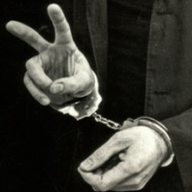 Father Berrigan flashes the peace sign at his arrest in Baltimore, 1968. Photo by Bob Fitch