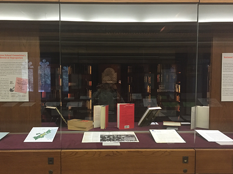 Materials for the exhibit laying in a display case in the Burns Library