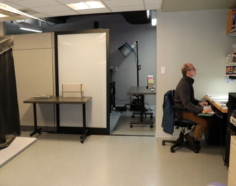 Jack Kearney, Digital Archives Specialist, working at a computer in the digitization lab, with a variety of other digitization equipment in the room.