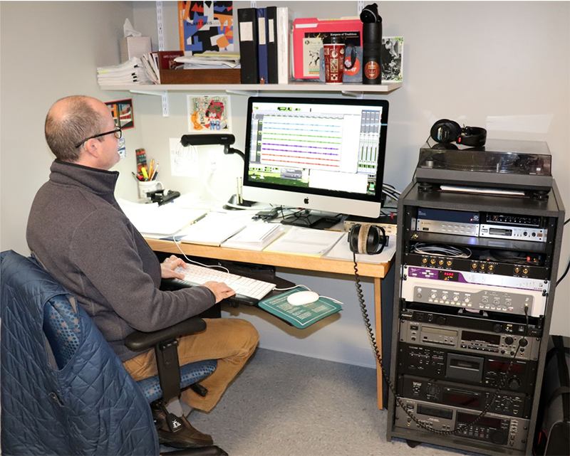 Jack Kearney capturing analog audio material in digital form. He is sitting at a computer whose wide monitor displays different colored audio waveforms. Next to him is a stack of 8 different audiovisual playback components.