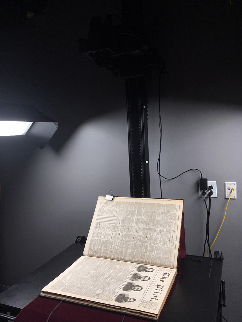 A full-page spread of a yellowing, old copy of the Boston Pilot under lights on a capture cradle, ready for photographing for digitization.