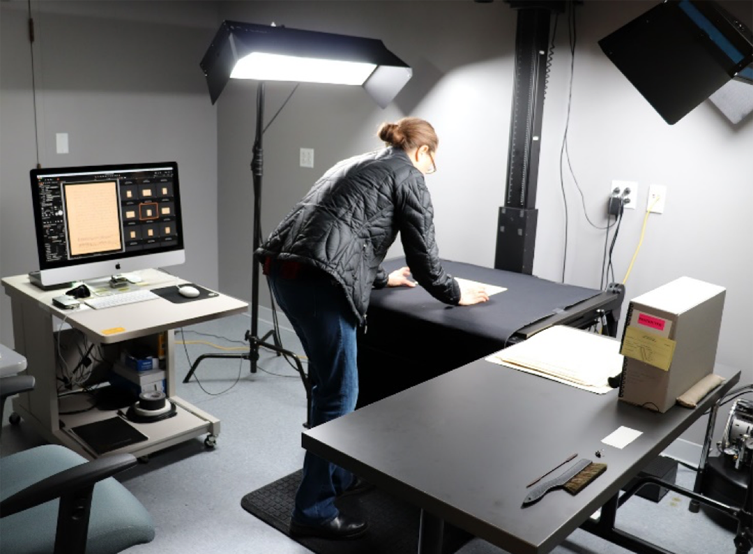Cheryl Ostrowski, Digital Content Specialist, adjusts a page from the Anansi stories on a flat black surface to capture a digital image with the Phase One Camera (out of sight at the top of this photo, because of the raised ceiling). The computer to the left shows recently digitized images.