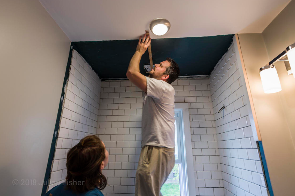 Photo of a man using measuring tape on ceiling while a woman watches from below. The room is under construction.