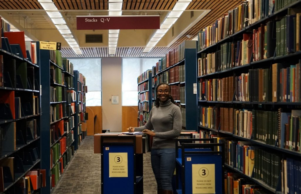 Lynda Musilwa, Morrissey '20, pulling books for scanning and ILL in O'Neill Library.