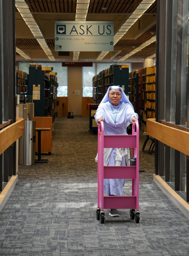 Sr. Maria Okeke, Lynch '20, pulling and shelving books for scanning and ILL in O'Neill Library.