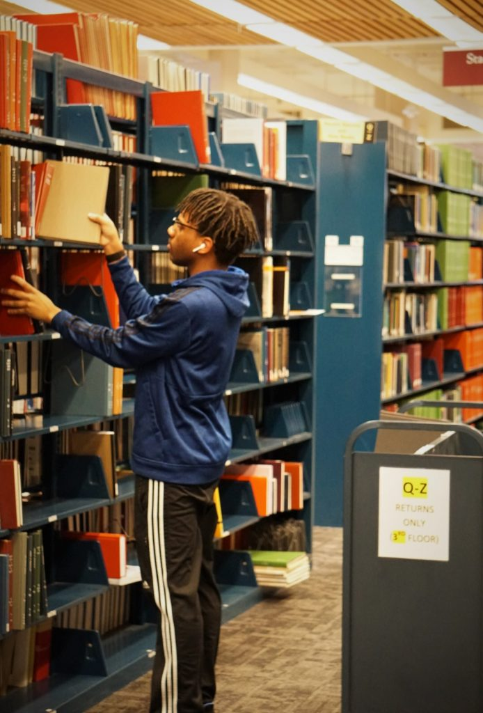 Valdon Sewell, Morrissey '22, pulling and reshelving books for ILL and scanning in O'Neill Library.