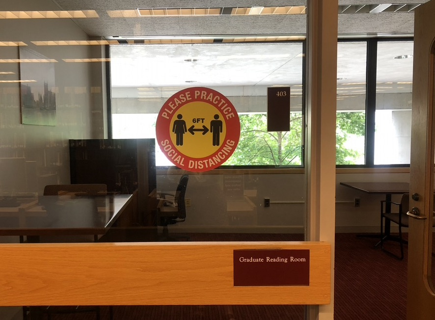 graduate reading room on O'Neill level 4, with round red and yellow social distancing poster