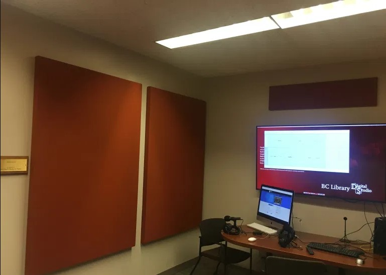 photo of the digital studio podcast room with red sound panels, wide-screen wall-mounted monitor, apple desktop, and microphones and headphones