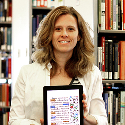 Photo of Melanie Hubbard holding an iPad with a background of books