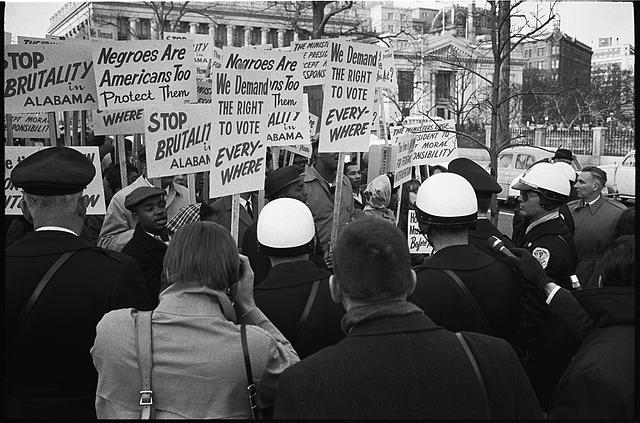 """Black and white image of a tight cluster of African American demonstrators outside the White House, with signs """"We demand the right to vote, everywhere"""" and signs protesting police brutality against civil rights demonstrators in Selma, Alabama"""
