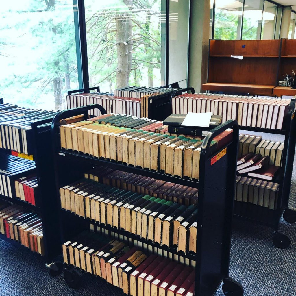 Six book carts full of periodical volumes await processing in TML, next to a window with a view of trees.