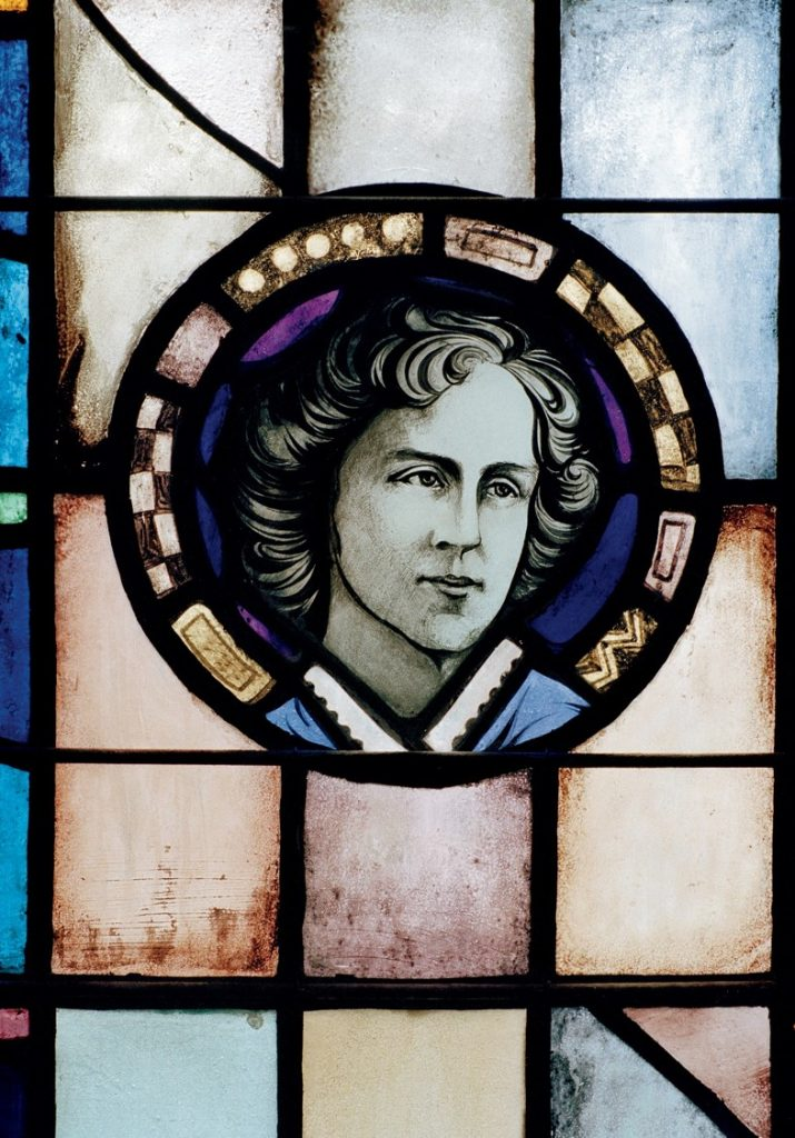 A stained glass portrait of Guiney's head surrounded by a purple and black patterned circle, with blue, red, and yellow square windowpanes around it.