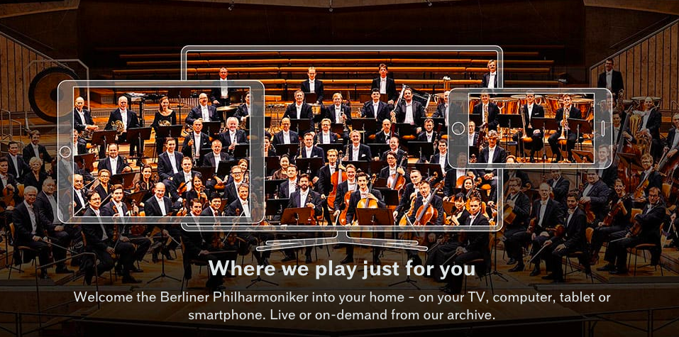 Berliner Philharmoniker home-page, showing the entire formally-clad Philharmoniker superimposed on semi-transparent outlines of a smartphone, a notebook pad, and a computer screen