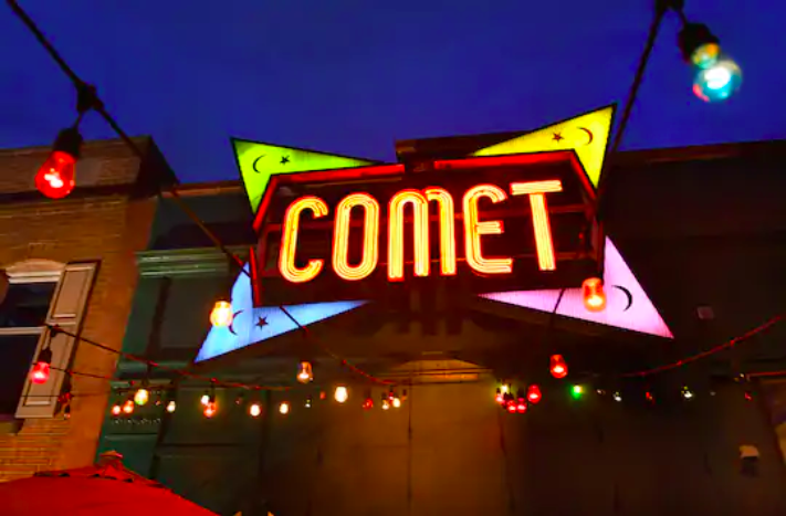 """The bright yellow, blue, pink, and green """"Comet"""" neon sign at the Comet Ping Pong restaurant on Connecticut Avenue NW in Washington in April 2020."""