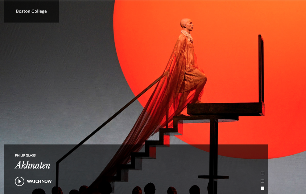 Dramatic image of character in an orange costume with a long train climbing stairs against a background of a large stylized orange sun in the Met staged opera of Akhnaten.