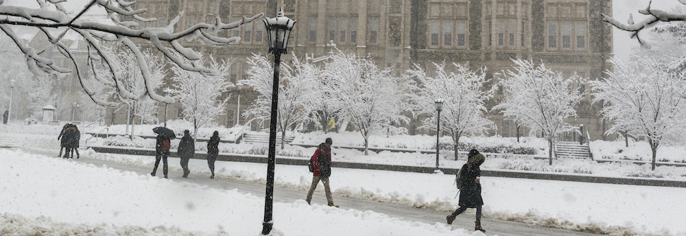 Silhouettes of people walking across the O'Neill Library quad at Boston College in the snow. Small trees are outlined in snow in front of Gasson Hall.