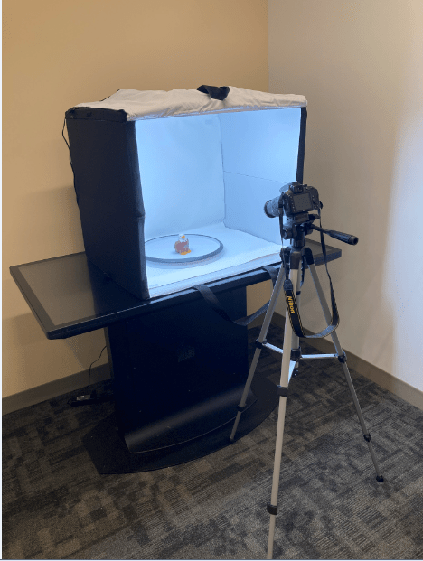 3d digital modeling station in the Digital Studio: a camera positioned on a tripod in front of a light-flooded box containing a small BC Eagle toy being imaged.