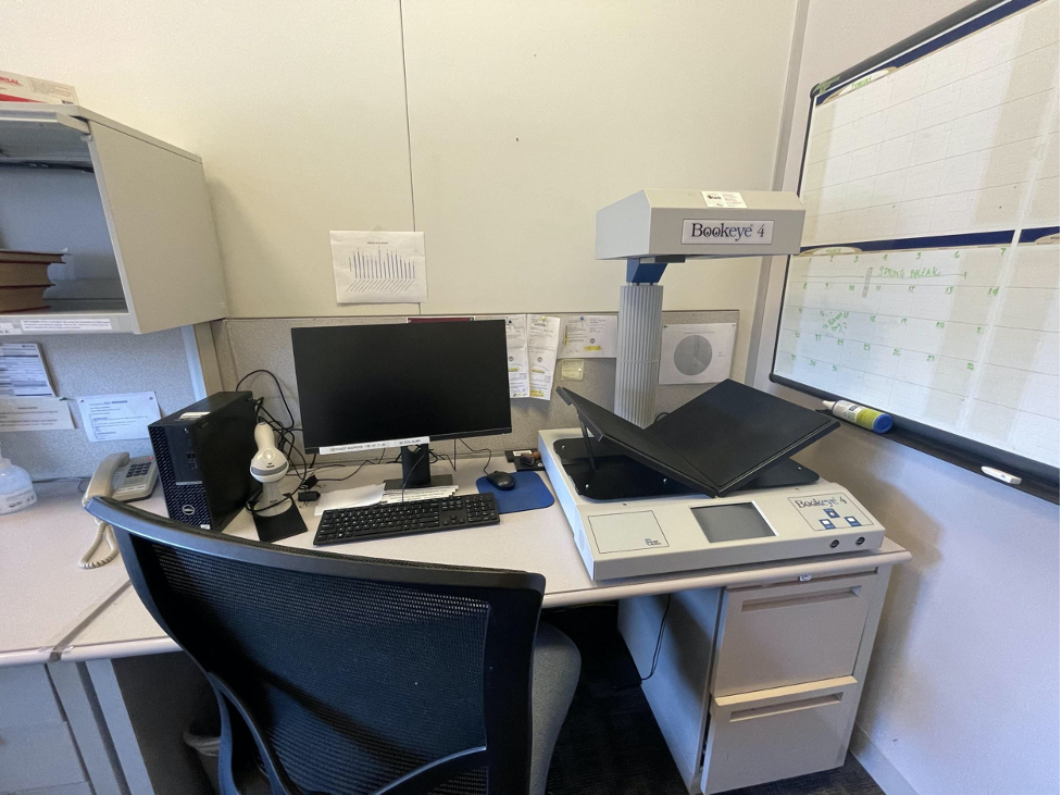 Photo of a desk with a computer and overhead scanner with an angled book tray in the ILL office.