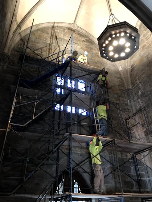 4 workmen in bright yellow shirts on 4 levels of scaffolding inside the Burns tower, dramatically backlit by two stained glass windows, with light cascading from a lamp above them. Workmen on lower levels are handing scaffolding supplies to the men above.