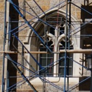 Blue scaffolding supports criss-cross in front of a neogothic window of Bapst Library.