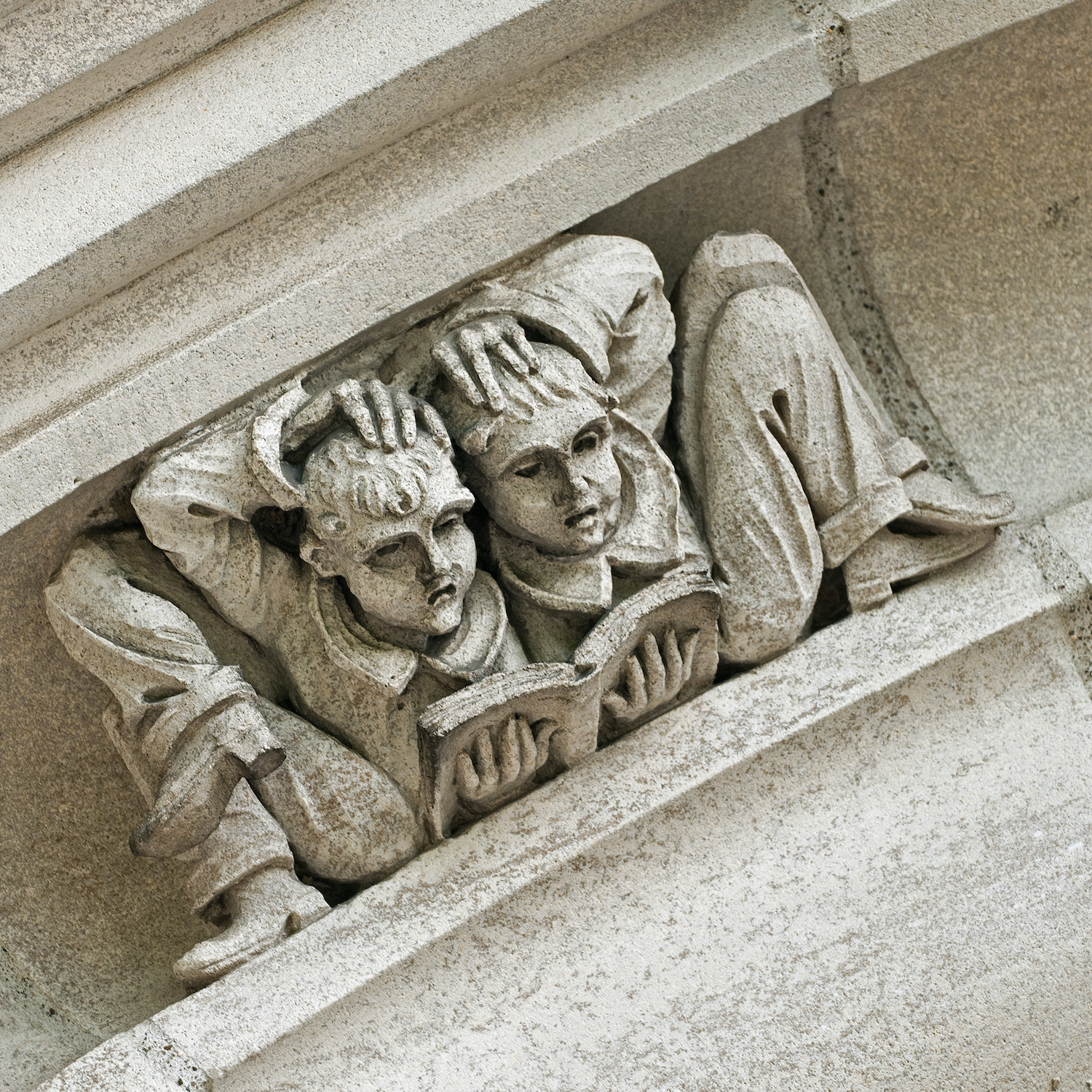 Detail of a whimsical gargoyle-like stonework figure of two students resting back to back while reading, and holding their heads in confusion.