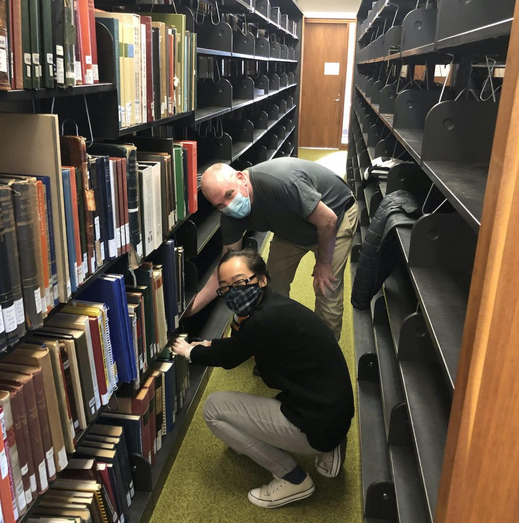 A man and a young woman crouch in a narrow library passage between shelves, both touching a book on the bottom shelf. Ranks of empty shelves are behind them. Both are wearing COVID pandemic masks.