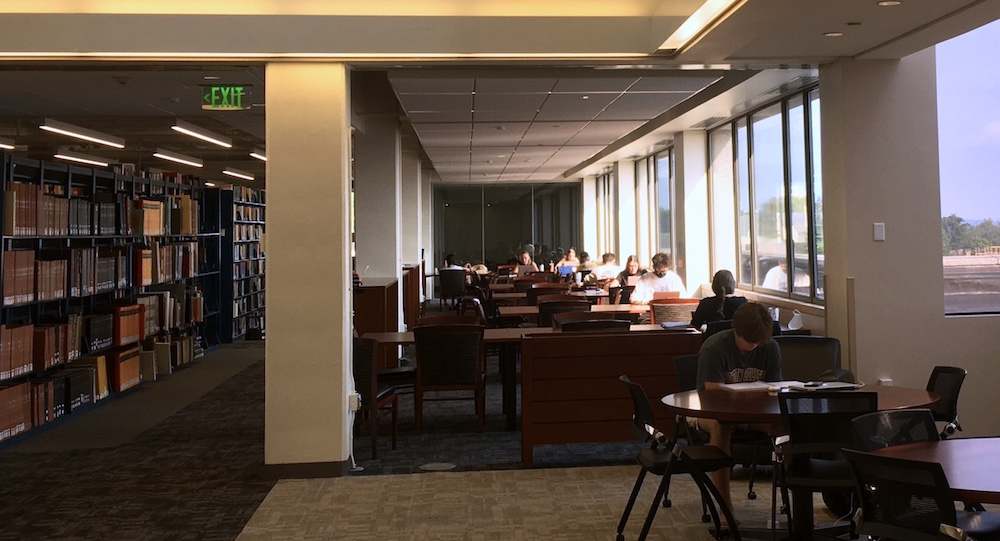 Several students seated at tables study intently in bright morning sun flooding through windows