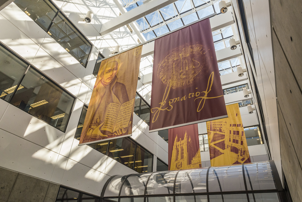 Bright morning sun streams through a large skylight into an atrium with red and yellow banners featuring St. Ignatius and Bapst and O'Neill Libraries.