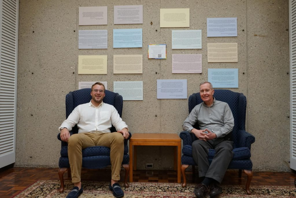 Two men in dark blue armchairs sit facing the camera; behind them are colored squares of paper covered in small print, mounted on a concrete wall.