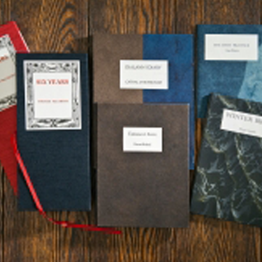 Photo of several poem books resting on a table