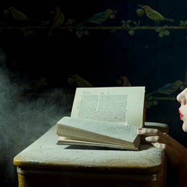 Photograph of a woman blowing dust off of a book