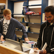 Two students checking in books